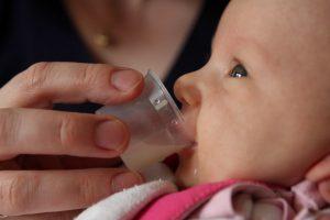 Cup feeding a newborn rather than using a bottle.